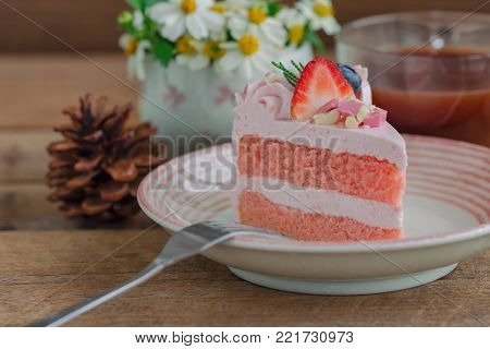 White chocolate strawberry yogurt cake decorated with fresh fruits and chocolate chunk. Sweet pink cake on wood table with copy space. Delicious and sweet pink cake for Valentines or birthday party. Homemade bakery concept. Sweet strawberry cake ready to