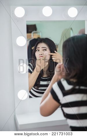 Acne treatment. Acne woman. Young woman squeezing her pimple, removing pimple from her face