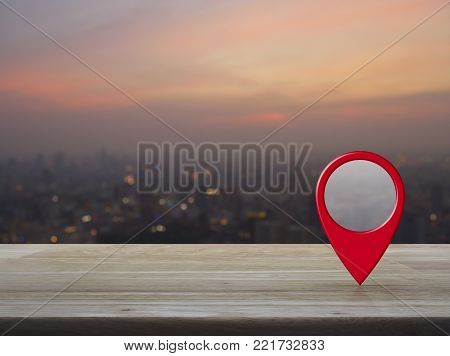 Map pin location button on wooden table over blur of cityscape on warm light sundown, Map pointer navigation concept