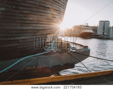 wooden historic viking boat in a beautiful warm sunset with flares in the port of Bergen in Norway