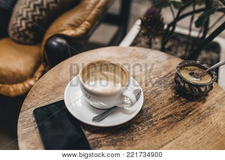almost empty cup of coffee with latte in a hipster café or restaurant on a wooden vintage round table with a smartphone and rustic interior in the background