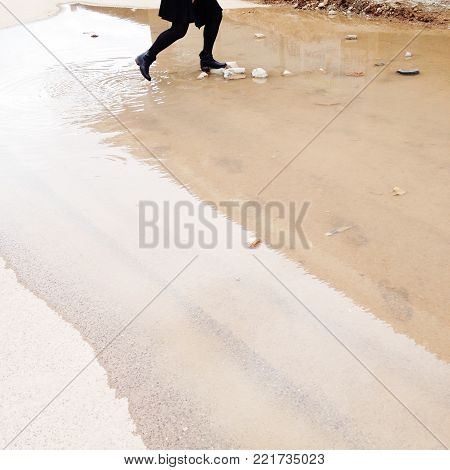young girl jumps into a huge puddle having fun playing while it's not raining