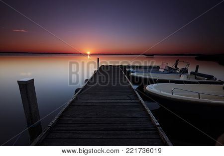 Small motorboats docked at a jetty in a calm lake under a red sunrise
