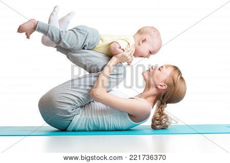 young mother does fitness exercises together with baby boy isolated on white