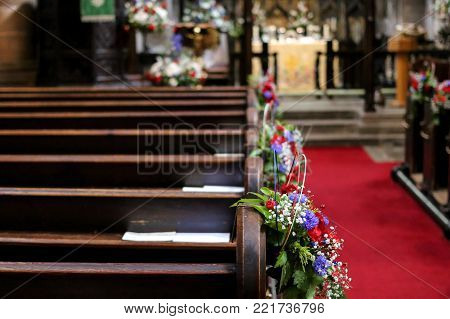 The wooden pews of the interior of the church with the flowers as decoration