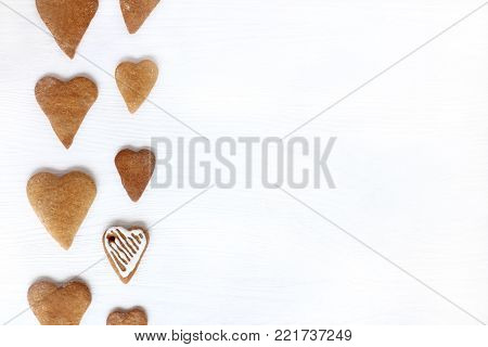 flat layout of cookies in the form of hearts one of which is not the same as all / baking is different from others