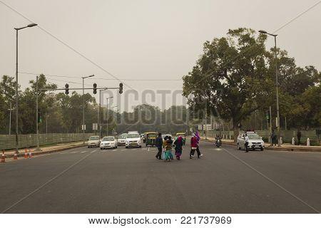 DELHI, INDIA - December 14 2014 : people walk crossing roadway at rajpath in winter season. this road is way to India gate.