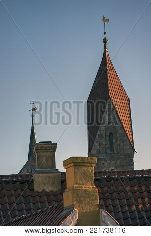 Cathedral tower and spire close to roofs and chimneys in Ribe, Denmark.