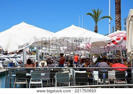 VILAMOURA, PORTUGAL - JUNE 6, 2017 - Tourists relaxing at a waterfront restaurant with yachts to the left hand side, Vilamoura, Algarve, Portugal, Europe, June 6, 2017.