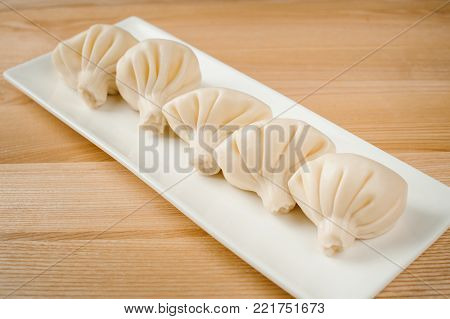 five delicious fresh khinkali, national dish of Georgian cuisine, appetizingly lined on a white ceramic plate