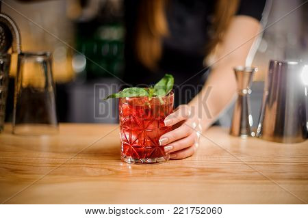 young pretty barmaid holds a crystal glass with a cocktail of red color