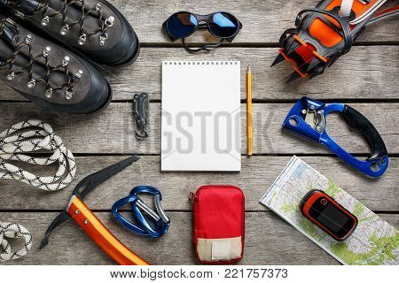 Top view of tourist equipment for a mountain trip on a rustic light wooden floor with a notebook, pencil and empty space in the middle. Items include glasses, a card, a multi-knife, a rope, a carbine, a flashlight, a first aid kit, an ice ax, a GPS, mount
