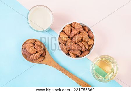 Peeled almonds with white bowl and cup of almond milk and oil on color paper background