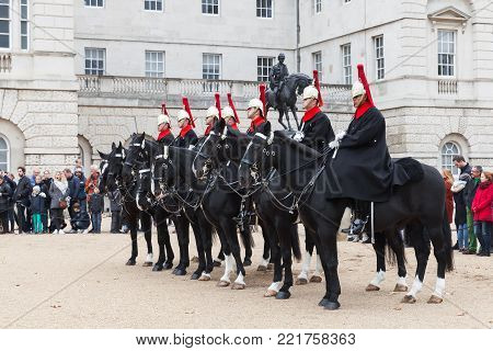 London, United Kingdom - October 29, 2017: Mounted guards outside Horse Guards off Whitehall in central London. Tourists watch the ceremony