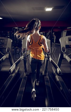 Rear View Of Attractive Shape Young Sporty Fitness Girl With A Ponytail Running On The Treadmill In