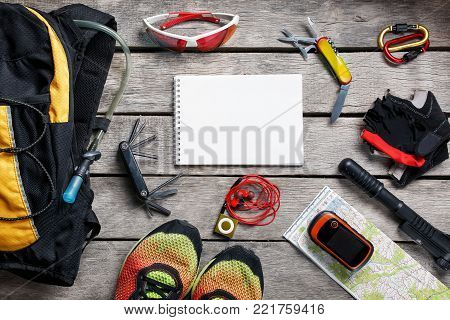 A set of accessories for cycling on a wooden background, With empty space and a notepad in the middle.