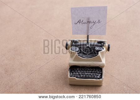 Retro syled tiny typewriter model on a brown background