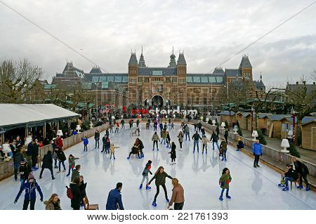 Amsterdam / Netherlands - January 1 2018: Panorama of the ice rink during the winter at Museumplein. In the background you can see the Rijksmuseum with words I Amsterdam.