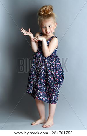 A shy girl on grey background with hairstyle