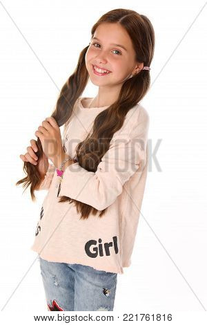 Portrait of beautiful happy brunette young teen girl in blue jeans. The adorable slender smiling preteen is an image of children's summer fashion. poster