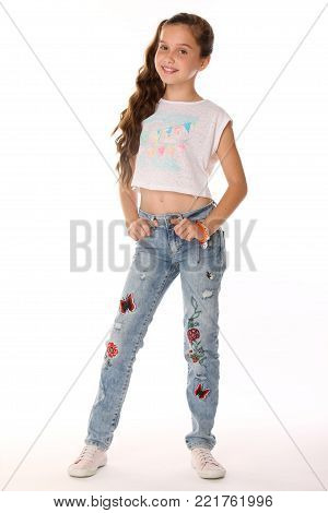 Pretty beautiful happy brunette young teen girl in blue jeans and a bare belly. The adorable slender smiling preteen standing on a white background. The image of children's summer fashion.