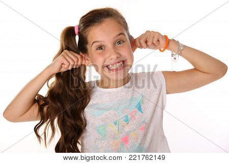 Portrait of beautiful cheerful brunette young teen girl builds a smiley face ape. The child playing tricks. Laughing preteen is an image of children's summer fashion. poster