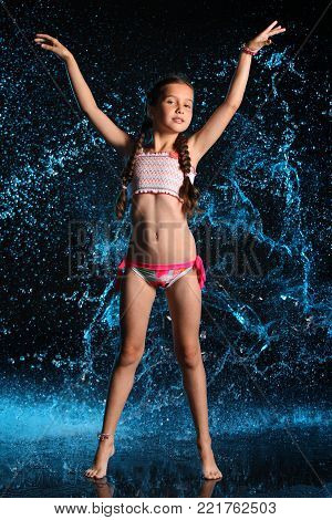 Adorable young teenage girl in a swimsuit stands barefoot in splashing water. Pretty child with dark hair, beautiful face and a slim figure. Slender preteen in a bikini. poster