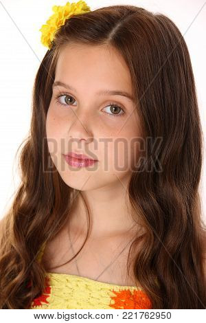 Portrait of a pretty young teenage girl close-up. Adorable preteen with dark hair, charming face and bare shoulders on a white background. The image of children's summer fashion.