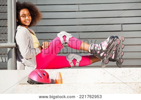 Side view portrait of preteen African girl wearing roller blades and protective gear, sitting on the stairs of outdoor rollerdrom