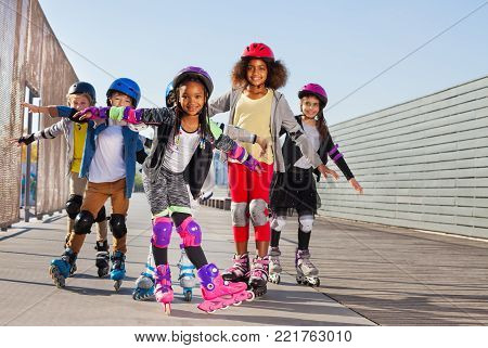 Portrait of preteen multiethnic boys and girls, happy roller skaters, standing with hands like wings at stadium outdoors