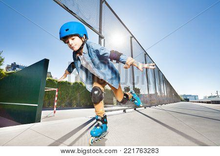 Portrait of preteen boy in roller blades and protective wear doing tricks with his hands like wings