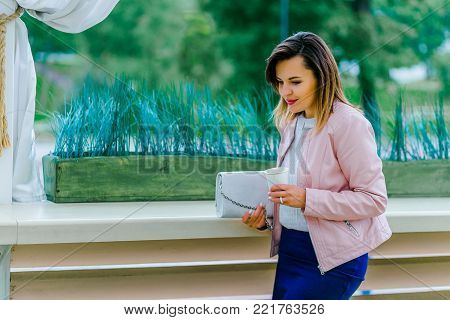 Portrait of beautiful caucasian woman with cup of coffee walking on a street