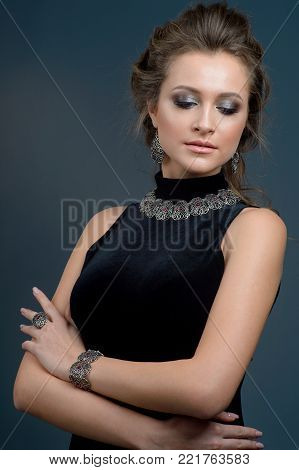 fashion portrait of Beauty Looks woman model with  brown hair fresh skin wearing accessories and jewelry isolated over dark blue background
