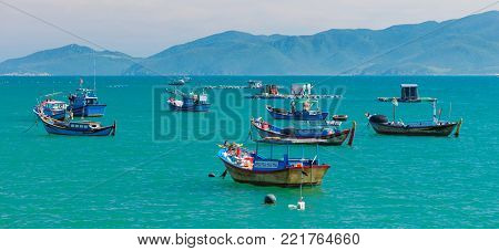 Vietnamese coastline looking out over the south china sea in Nha Trang Vietnam with a turquoise ocean and fishing boats.