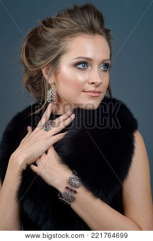 Beautiful young girl in an expensive fur coat with luxurious silver jewelry