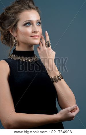 Beautiful brunette woman with perfect skin, bright makeup and  jewelry. Beauty face. Picture taken in the studio on a dark blue background