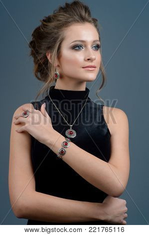 Jewelry concept. Beauty portrait of a beautiful female model posing isolated on a dark blue background
