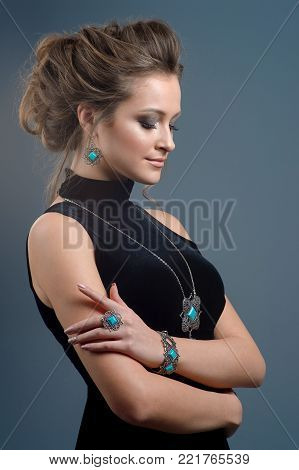 Bohemian style. Portrait of a beautiful sensual woman on dark blue background. Beauty, fashion. Jewelry.