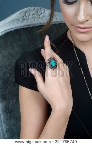 close-up woman hand with ring on finger and necklace on background