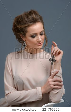 Fashion portrait of young beautiful woman with jewelry. Brown hair girl. Perfect makeup. Beauty style girl with accessories