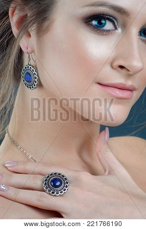 close-up studio portrait model demonstrate stylish finger ring and earring. Winter jewelry collection of silver accessory