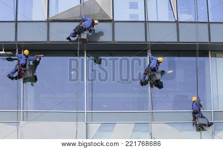 Dubai, United Arab Emirates, January 12th, 2018: workers hanging down a buiding to wash windows