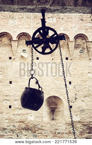Metal bucket on a pulley hanging in the courtyard of the historic palace, Siena, Tuscany, Italy. Old photo filter.