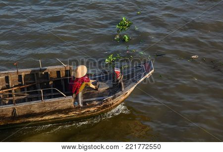 A woman sitting on wooden boat in Mekong Delta, Vietnam.