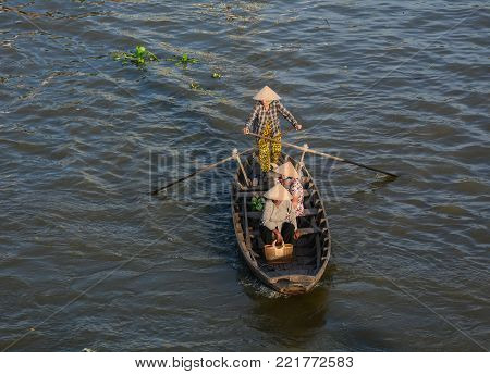 Soc Trang, Vietnam - Feb 2, 2016. Women rowing wooden boat on Mekong River in Soc Trang, Vietnam. Mekong is the world 12th-longest river and the 7th-longest in Asia.