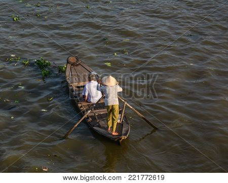 A woman rowing wooden boat on Mekong River in Soc Trang, Vietnam.