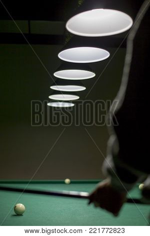 The Man Is Holding A Cue In Front Of The Billiards Table.