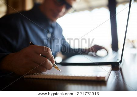 Casual man or student working on laptop and writing on paper notebook. Young businessman in glasses taking notes in notepad with stylish premium expensive fountain pen. Business theme. Male signing contract.