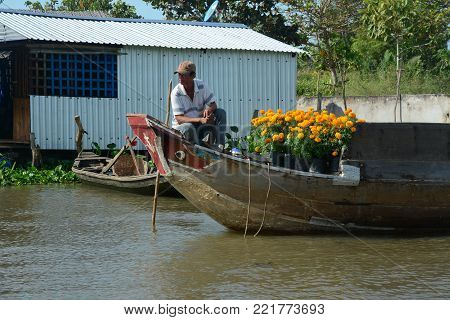 Soc Trang, Vietnam - Feb 2, 2016. A man selling flowers on Mekong River in Soc Trang, Vietnam. Mekong is the longest river in Southeast Asia, the 7th longest in Asia.