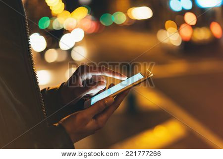 Girl texting finger on screen smartphone on background illumination glow bokeh light in night atmospheric city, hipster using in female hands mobile phone; mockup glitter street, content internet concept